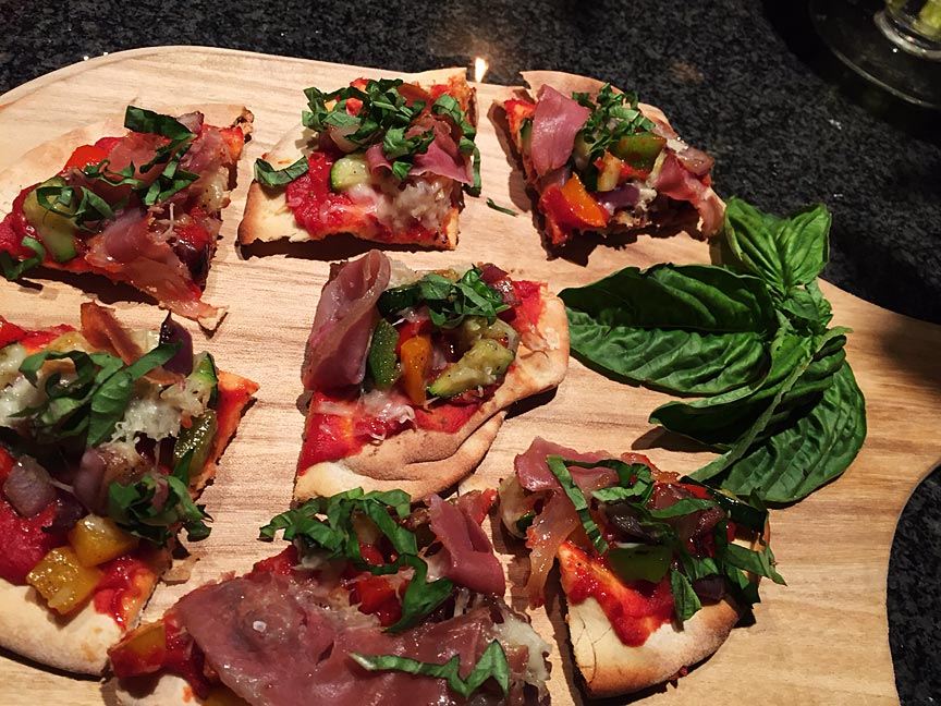 Appetizer Pizzettas topped w/ grilled vegetables & Prosciutto